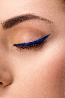 partial view of closed female eye with blue eyeliner and perfect skin