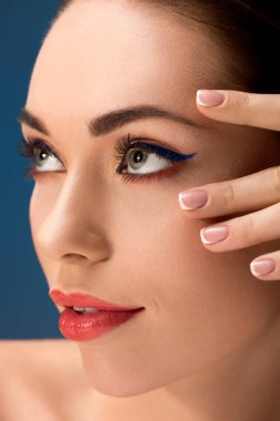 portrait of beautiful woman with glamorous makeup touching face isolated on blue