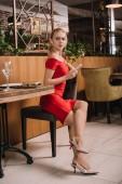 atraktivní žena v červených šatech sedí v restauraci a čeká na člověka
