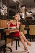 atraktivní žena v červených šatech, posezení v restauraci, pomocí smartphone a čeká na člověka