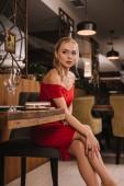 atraktivní dívka v červených šatech sedí v restauraci a čeká na přítele