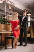 handsome man helping to sit down attractive woman in restaurant