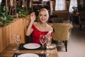 atraktivní žena v červených šatech sedí v restauraci mává rukou