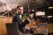 pohledný muž, který držel sklenici s červeným vínem při posezení v restauraci