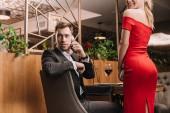 handsome man talking on smartphone near girlfriend in red dress