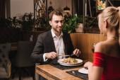 handsome man having dinner with girlfriend in restaurant