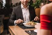 oříznutý pohled člověka na večeři s přítelkyní v restauraci