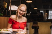 cheerful blonde woman writing on paper and smiling in restaurant