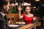 šokovaná žena házení ubrousek na přítele v restauraci