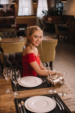 attractive woman in red dress sitting in restaurant and smiling at camera