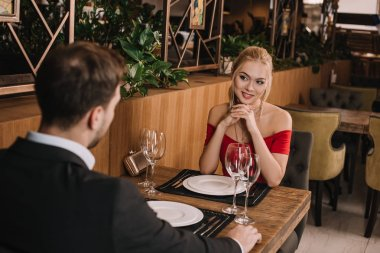 Attractive girlfriend in red dress looking at boyfriend in restaurant stock vector