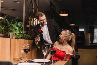 Handsome boyfriend giving red rose to surprised girlfriend in restaurant stock vector