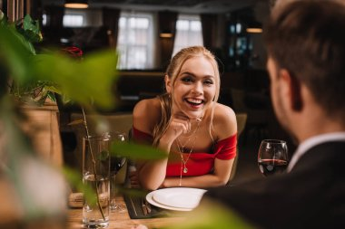 Selective focus of cheerful girl looking at man and laughing in restaurant stock vector