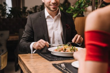 cropped view of man having dinner with girlfriend in restaurant