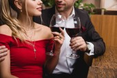 oříznutý pohled muže a ženy držící brýle s červeným vínem