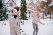 Veselý pár si hraje s sněhové koule v zimě