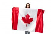 Fotografie smiling woman holding canadian flag isolated on white
