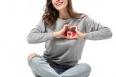 Fotografie cropped view of woman showing heart symbol with hands over canadian flag badge isolated on white
