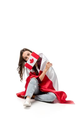 woman covered in canadian flag holding maple leaf flag in front of face isolated on white