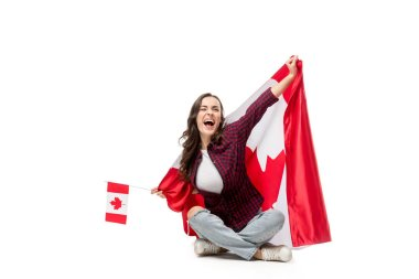 excited woman covered in canadian flag holding maple leaf flag isolated on white
