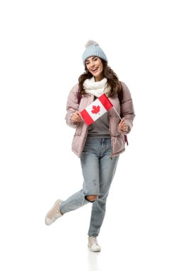 happy female student in winter clothes holding canadian flag isolated on white