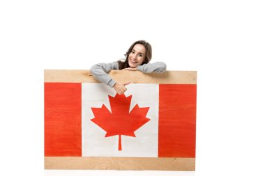 woman sitting behind wooden board with canadian flag and showing thumb up sign isolated on white