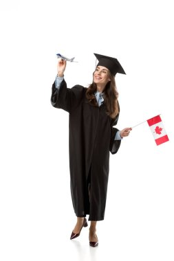 smiling female student in academic gown holding canadian flag and plane model isolated on white, studying abroad concept