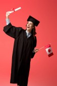 happy female student in academic gown holding canadian flag and diploma isolated on living coral