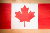 Fotografie top view of canadian flag on wooden background