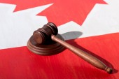 selective focus of wooden gavel with canadian flag on background, justice concept