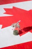 Selektivní fokus konopí do sklenic s kloubem na kanadské vlajce, koncept legalizace marihuany