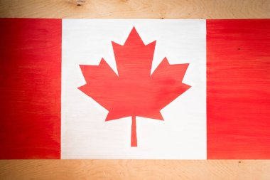 top view of canadian flag on wooden background