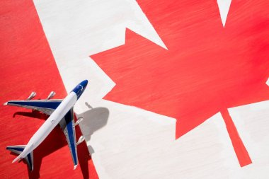 plane model with canadian flag on background, immigration concept