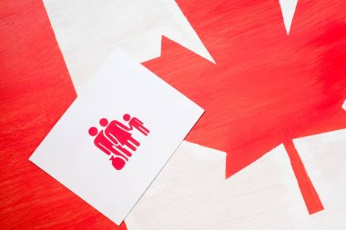 white card with family icon on canadian flag, immigration concept