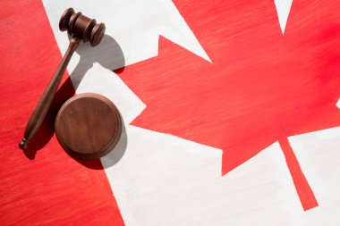 wooden gavel with canadian flag on background, justice concept