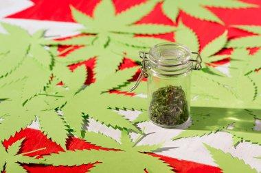 paper marijuana leaves on canadian flag with cannabis in glass jar, marijuana legalization concept