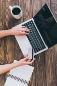 Draufsicht der Frau mit Laptop und Kreditkarte in der Nähe einer Tasse Kaffee