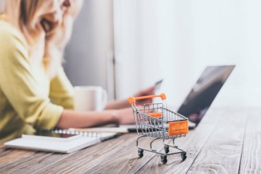 selective focus of small shopping trolley with woman using laptop on background