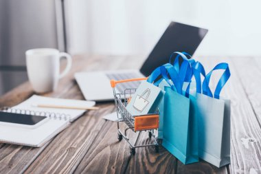 selective focus of small shopping bags near toy shopping trolley with laptop on background