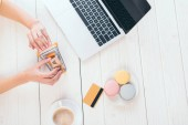 top view woman holding toy shopping trolley with small paper boxes near laptop, cup and macaroons