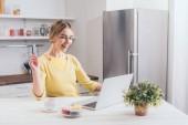 Fotografie šťastná žena držící kreditní kartu při pohledu na notebook v kuchyni