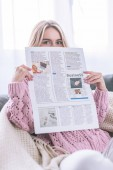 woman reading business newspaper while sitting at home