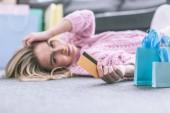 selektiver Fokus der Kreditkarte in der Hand einer Frau, die zu Hause auf dem Boden liegt