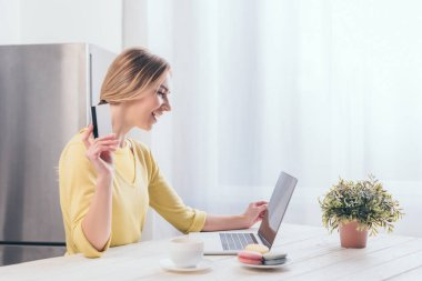 cheerful woman holding credit card while looking at laptop