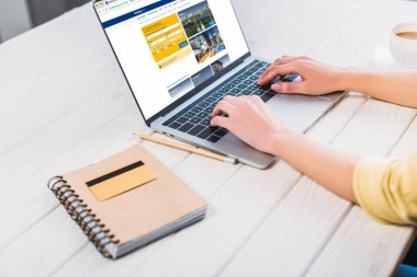 cropped view of woman using laptop with booking website on screen
