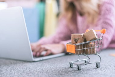 selective focus of small cart with toy paper boxes with woman using laptop on background