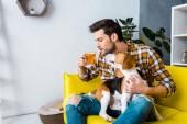 příležitostné muž, pití čaje a sedí na pohovce s roztomilý pes
