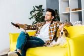 příležitostné muž s dálkovým ovládáním, sledování televize a sedí na pohovce se psem