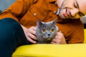 casual cheerful man with british shorthair cat at home