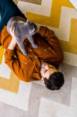 top view of handsome man lying on carpet with british shorthair cat